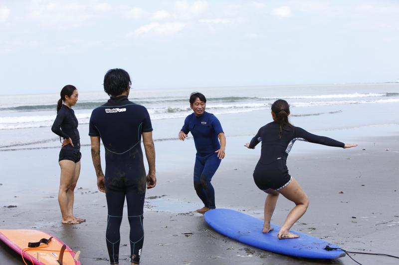 サーフィボード上での姿勢を教えるサーフィンスクールの様子